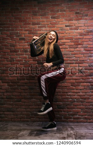 Full length image of caucasian woman 20s standing against brick wall and holding boombox #1240906594
