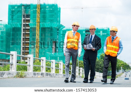 Full-length image of constructor engineers walking and discussing the project outdoors