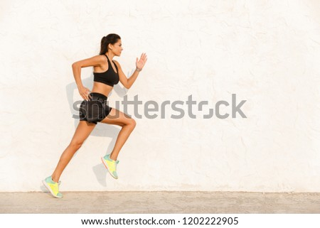 Full length image of fitness girl 20s in sportswear working out and running along wall