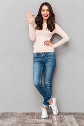 Full-length image of gorgeous female in jeans smiling and gesturing on camera with OK symbol, expressing good choice over gray background