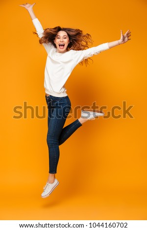 Full length image of Happy brunette woman in sweater jumping and looking at the camera over yellow background