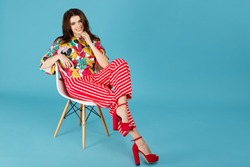 Full length image of pretty bright brunette woman in colorful casual clothes sitting on the chair on the blue background.