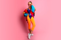 Full length image of 80's Fashion woman over pink background. Beautiful athletic girl in 80s style sportswear, fashionable woman in bright body suit