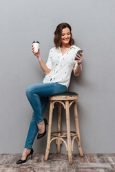 Full length image of Smiling woman posing on chair with cup of coffee in hand and using smartphone over gray background