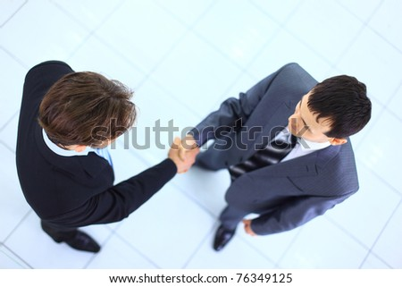 Full length image of two successful business men shaking hands with eachother