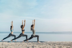 Full length image of young multiethnic group of woman practicing yoga exercise at the beach near water