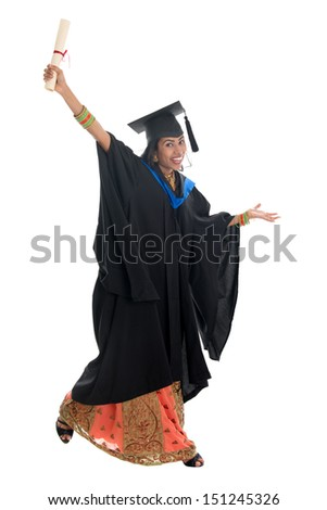 Full length Indian university student in graduation gown holding diploma certificate jumping. Portrait of mixed race Asian Indian and African American female model standing isolated white background.