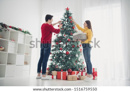 Full length low angle view photo of two romantic people decorate cristmas evergreen tree hang balls toys prepare for noel celebration enjoy x-mas atmosphere in house indoors #1516759550