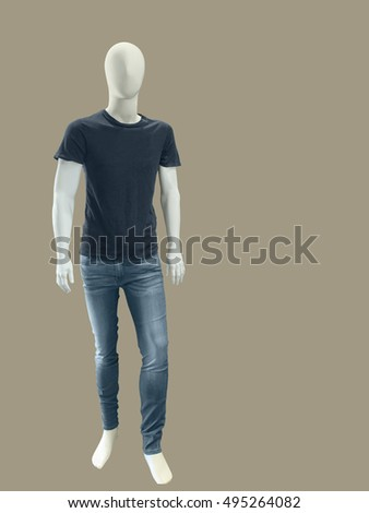 Full length male mannequin dressed in t-shirt and jeans, isolated on brown background. No brand names or copyright objects.