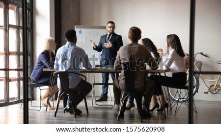 Full length male speaker presenting project financial analysis or corporate marketing strategy on flipchart to focused managers at office. Presenter holding educational workshop to diverse colleagues.