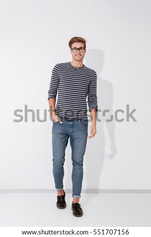 Full length man in striped sweater and glasses posing with arm in pocket on gray background in studio #551707156