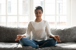 Full length mindful young indian woman making mudra gesture, sitting in lotus position on comfortable couch at home. Peaceful millennial girl deeply meditating, doing breathing yoga exercises alone.