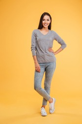 Full length model in studio. smiling young girl looking at camera. arm at hip