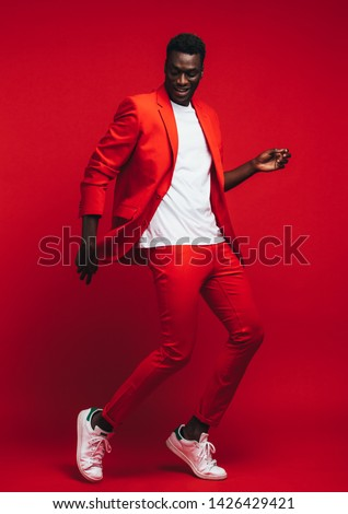 Full length od handsome young african man dancing on red background. Man in stylish red outfit showing some dance moves.