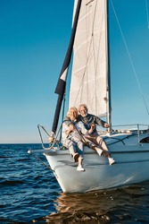 Full length of a beautiful and happy senior family couple embracing and smiling at camera while relaxing on a sail boat or yacht deck floating in a calm blue sea