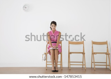 Full length of a beautiful young woman in pink dress sitting at waiting room