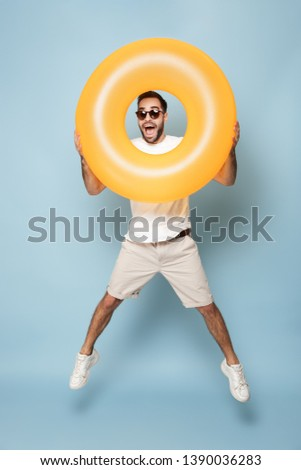 Full length of a cheerful excited man wearing blank t-shirt jumping isolated over blue background, having fun with inflatable ring #1390036283