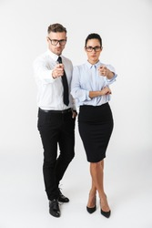 Full length of a colleagues couple wearing formal clothing standing isolated over white background, pointing fingers