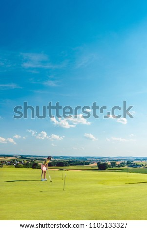 Full length of a determined young woman practicing golf moves and strikes on the grass of a training area for putting green, in an idyllic sunny rural place #1105133327