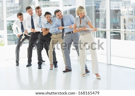 Full length of a group of business people pulling rope in a bright office