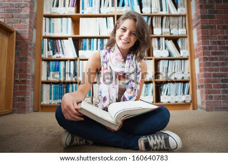 Full length of a happy female student sitting against bookshelf with a book on the library floor