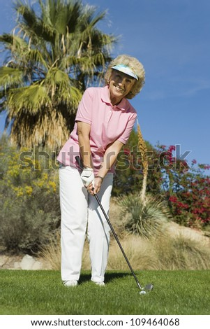 Full length of a happy senior woman playing golf at golf course