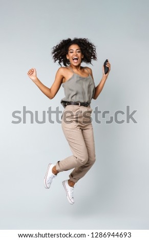 Full length of a happy young african woman casually dressed jumping isolated over gray background, holding mobile phone