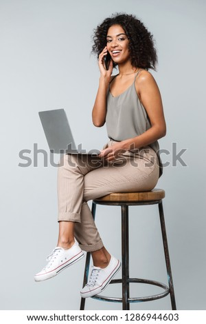 Full length of a happy young african woman casually dressed sitting on a chair isolated over gray background, working on laptop computer, talking on mobile phone