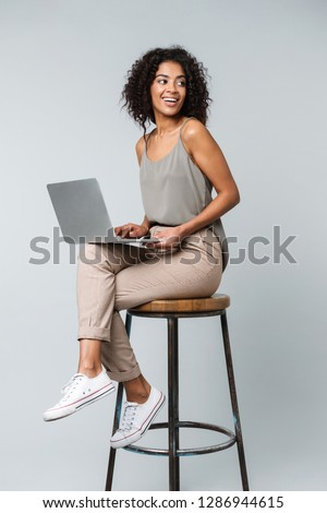 Full length of a happy young african woman casually dressed sitting on a chair isolated over gray background, working on laptop computer