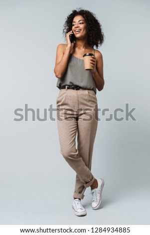 Full length of a happy young african woman casually dressed standing isolated over gray background,talking on mobile phone, holding takeaway cup of coffee