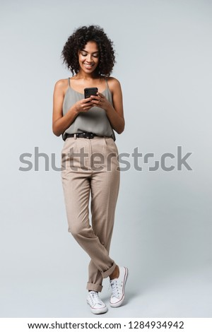 Full length of a happy young african woman casually dressed standing isolated over gray background, holding mobile phone