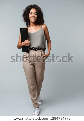 Full length of a happy young african woman casually dressed standing isolated over gray background, holding a notepad