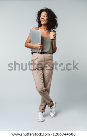 Full length of a happy young african woman casually dressed standing isolated over gray background, carrying laptop computer, holding takeaway cup