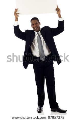 Full length of a happy young black businessman holding blank sign above his head - copyspace isolated over white background