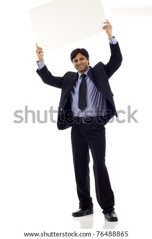 Full length of a happy young Indian businessman holding blank sign above his head - copyspace isolated over white background