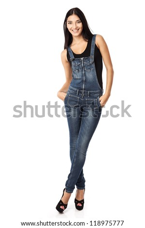 Full length of a happy young woman standing with hands in pockets over white