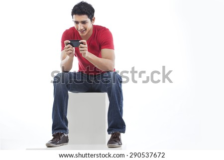 Full length of a man using phone for text messaging against white background #290537672