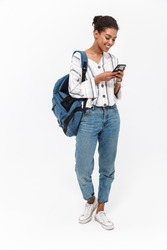 Full length of a portrait of an attractive young african woman carrying backpack standing isolated over white background, using mobile phone