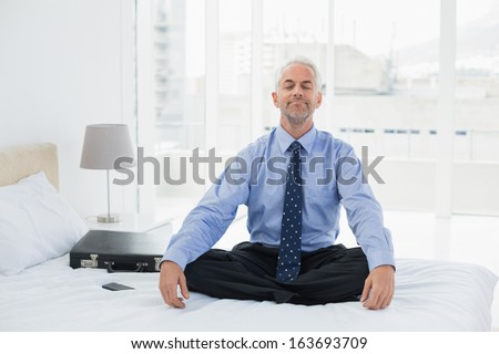 Full length of a relaxed mature businessman sitting with eyes closed on bed at home