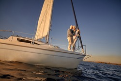 Full length of a romantic retired couple, senior man and woman standing on the side of sail boat or yacht deck floating in the calm blue sea, hugging and enjoying amazing sunset