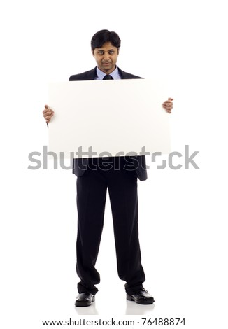 Full length of a serious looking young Indian businessman holding blank sign  - copyspace isolated over white background