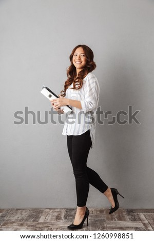 Full length of a smiling asian business woman standing over gray background