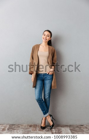 Full length of a smiling young asian woman standing and looking at camera over gray background