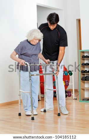 Full length of a trainer assisting senior woman in moving walker