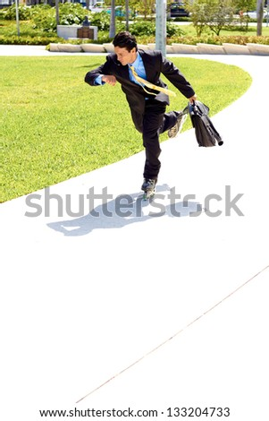 Full length of a young businessman rollerblading with briefcase in urgency while checking the time. Horizontal shot.