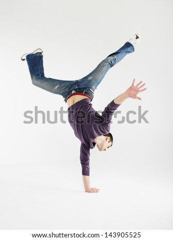 Full length of a young man doing one handed handstand against gray background
