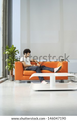 Full length of a young man using laptop on orange sofa in reception room at office
