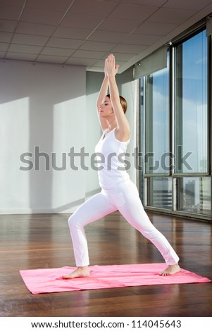 Full length of a young woman performing Crescent Moon pose on mat