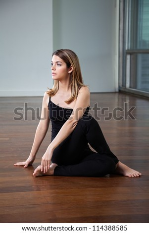 Full length of a young woman practicing yoga called Half Spinal Twist on wooden floor