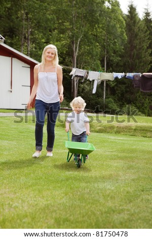 Full length of adorable child pushing a wheelbarrow in garden while walking with mother